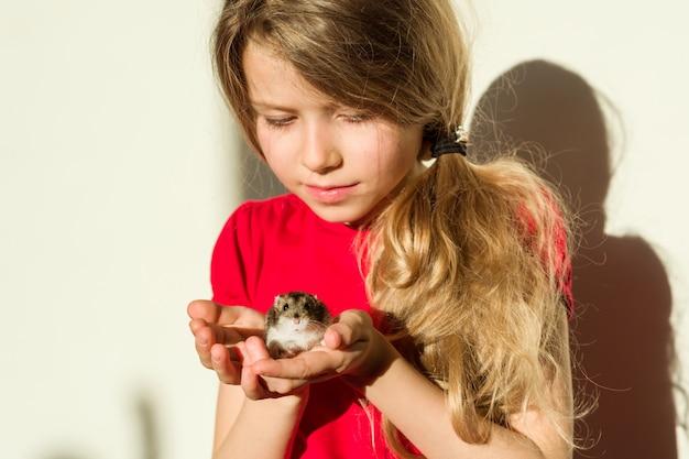 Het meisjeskind houdt in handen van haar geliefde huisdierenhamster