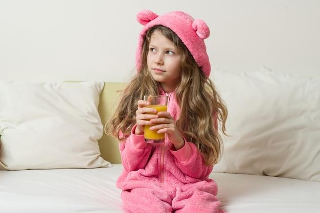 Het meisjeskind in een pyjama met een kap thuis en drinkt jus d'orange