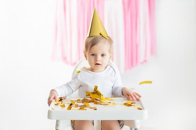 Het meisjeskind werpt vrolijk kleurrijk klatergoud en confettien op een grijze blauwe achtergrond op. vakantie. gelukkig opgewonden lachende baby op verjaardag.