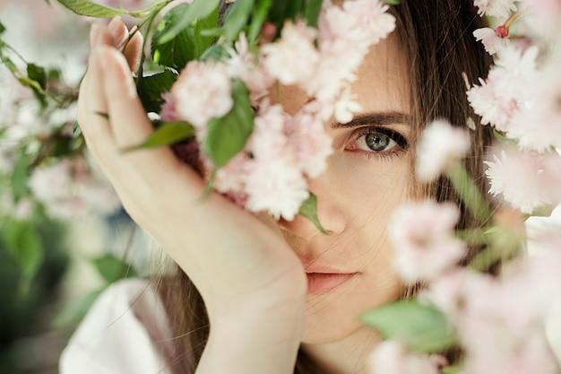 Het meisjesportret onder sakura bloeit dicht omhoog