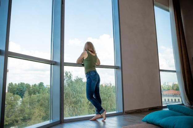 Het meisjessilhouet dichtbij van groot vensterglas ziet buiten aan gebouwen sity. dromen. hartproblemen. problemen. panoramische windows. achteraanzicht. kopie ruimte