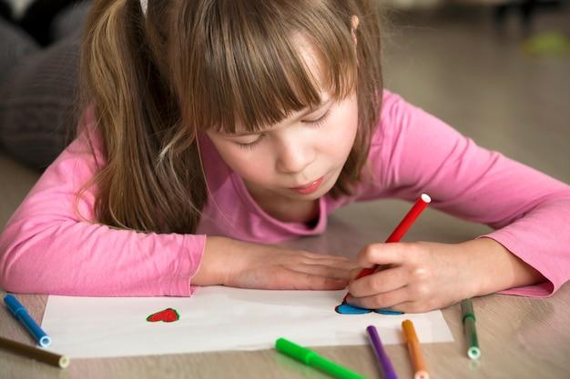 Het meisjestekening van het kind met het kleurrijke hart van potlodenkleurpotloden op witboek. kunsteducatie, creativiteit.
