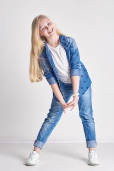 Het meisjestiener van de blonde in een denimkostuum, pretkind