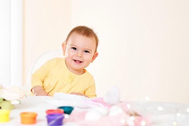 Het meisjeszitting van de baby bij de lijst en het schilderen vakantiepaaseieren die gelukkige kinderjaren glimlachen