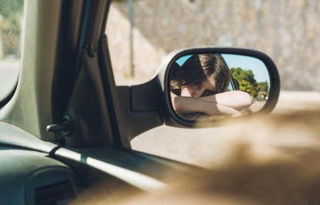 Het meisjeszitting van de tiener in de auto op een de zomermiddag