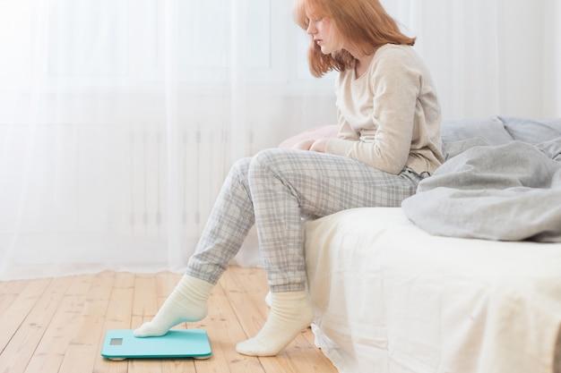 Het meisjeszitting van de tiener op bed en schaal op vloer