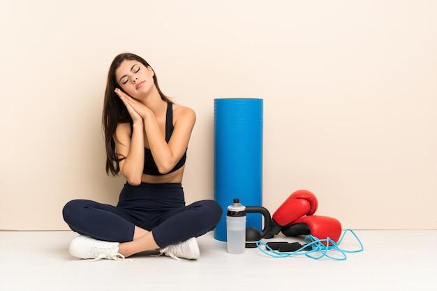 Het meisjeszitting van de tienersport op de vloer die slaapgebaar in dorable uitdrukking maken
