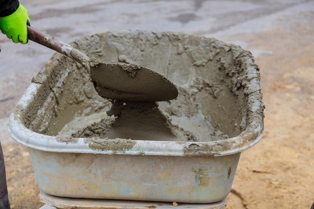 Het mengen van het cement in een dienblad bij bouwwerf