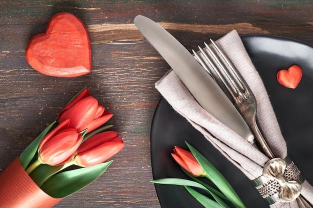 Het menuconcept van de lente met lichtgeel bord en bestek dat met verse tulpen op donker hout wordt verfraaid