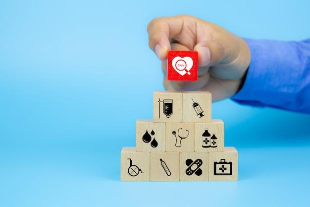 Het met de hand plukken van gezondheidspictogram op kubus houten speelgoed blokkeert stapel in piramidevorm met andere medische pictogrammen.