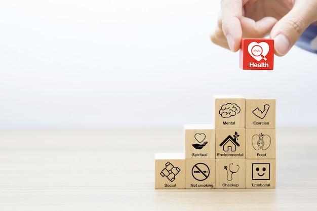 Het met de hand plukken van medisch en gezondheidssymbool op een houten stuk speelgoed blok.