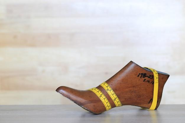 Het meten van band op houten laatste schoen op houten achtergrond