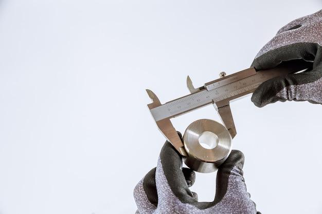 Het meten van binnendiameter, buitendiameter, lengte met een schuifmaat op wit