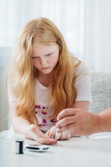 Het meten van bloedsuikerspiegel van droevig tienermeisje met glucometer