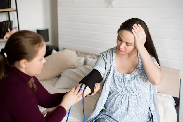 Het meten van de druk van een zwangere vrouw thuis