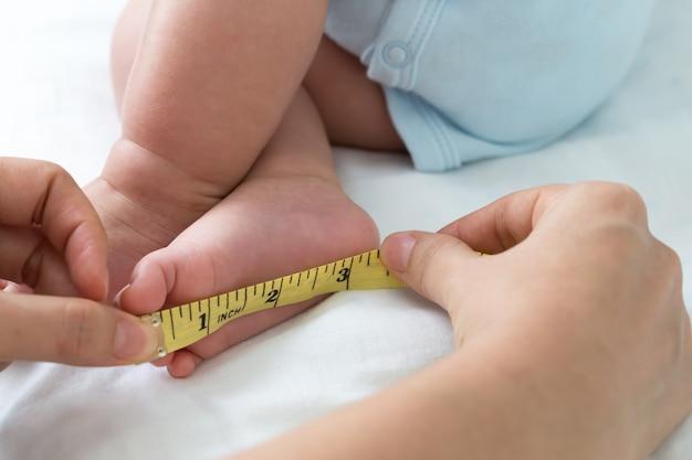 Het meten van de grootte van de voetbaby, het concept van het zuigelingslichaam, drie maanden oud