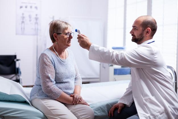Het meten van de temperatuur van een oude senior vrouw tijdens overleg in de onderzoekskamer van de kliniek