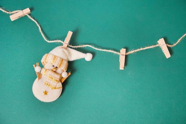 Het miniatuur grappige het stuk speelgoed van kerstmis sneeuwman hangen op de wasknijpers