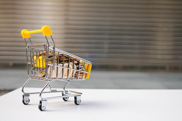 Het miniboodschappenwagentje bevat stapelmuntstukken die als e-commerce en bedrijfsmarketingconcept gebruiken