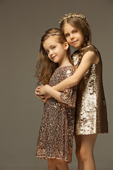 Het mode-portret van jonge mooie tiener meisjes in gouden jurk. de concepten beauty, fashion, glow, make-up en shinning. kaukasische modellen