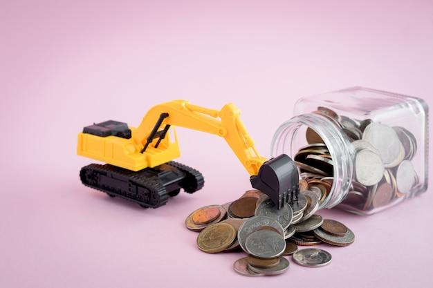 Het model van de graafmachine loader met stapel munten in de glazen pot, bespaart geld, investeringen, zaken en financiën concept