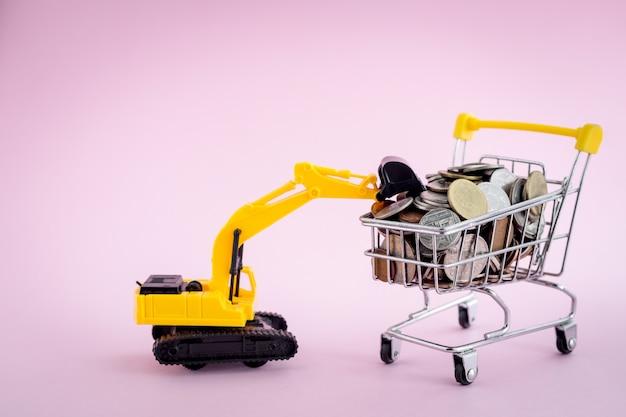 Het model van de graafmachine loader met stapel munten in het winkelwagentje, waardoor geld, investeringen, zaken en financiën concept worden bespaard