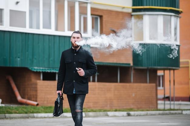 Het model vaper vapen van een verdamper buitenshuis. veilig roken. jonge vaper.