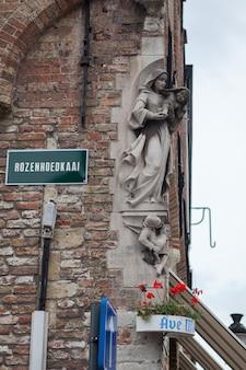 Het moderne standbeeld van madonna aan de rand van het huis. brugge belgië