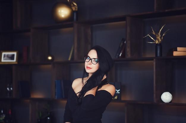 Het modieuze bedrijfsvrouw stellen in donker binnenland
