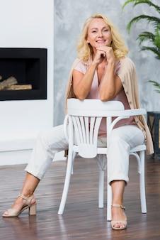 Het modieuze blondedame stellen op witte stoel