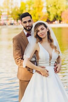 Het modieuze gelukkige bruid en bruidegom stellen bij groot liefdewoord in avondlicht bij huwelijksontvangst in openlucht. schitterend huwelijkspaar van jonggehuwden die pret in avondpark hebben.