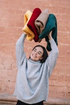 Het modieuze jonge meisje die een gebreide grijze sweater dragen glimlacht en geniet van terwijl het houden van kleurrijke sweaters