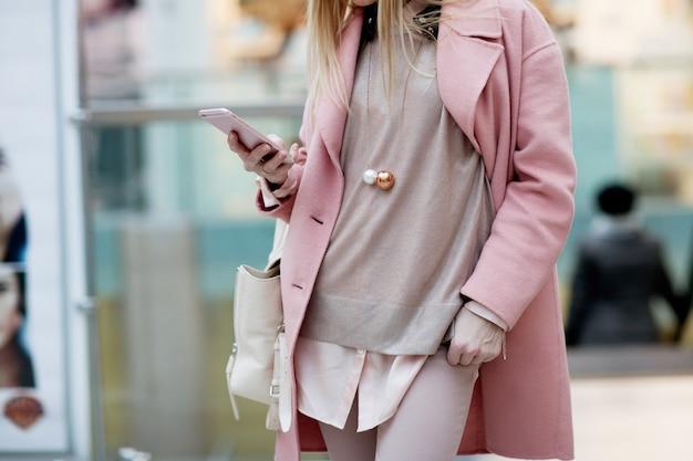 Het modieuze jonge meisje die zich in een roze laag in een winkel bevinden en onderzoekt de telefoon