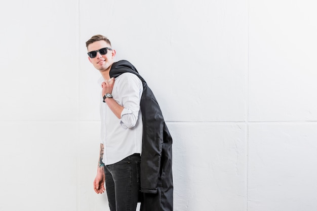 Het modieuze knappe jasje die van de jonge mensenholding over zijn schouder camera tegen witte muur bekijken