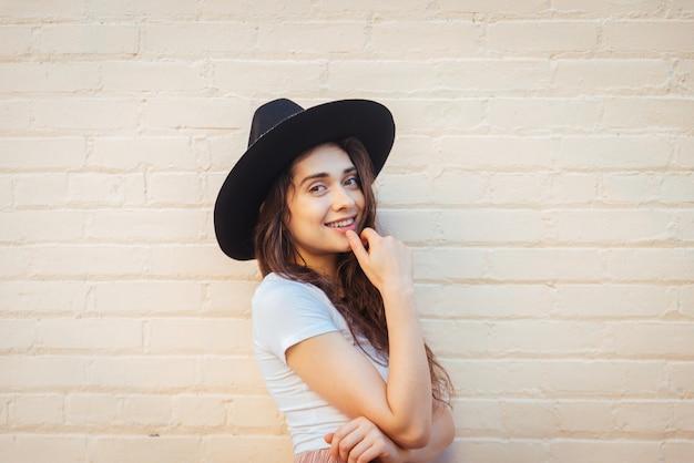 Het modieuze mooie tienervrouw stellen met hoed