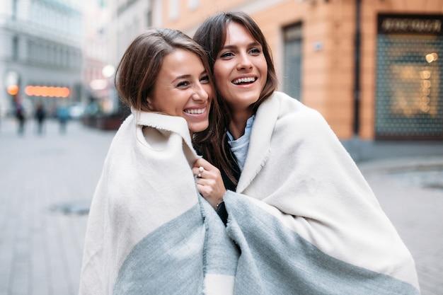 Het modieuze portret van de close-upstraat van twee meisjesvrienden die samen glimlachend en het hebben van pret stellen