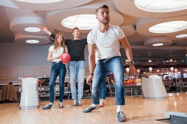 Het moet een staking zijn. jonge, vrolijke vrienden vermaken zich in het weekend in de bowlingclub