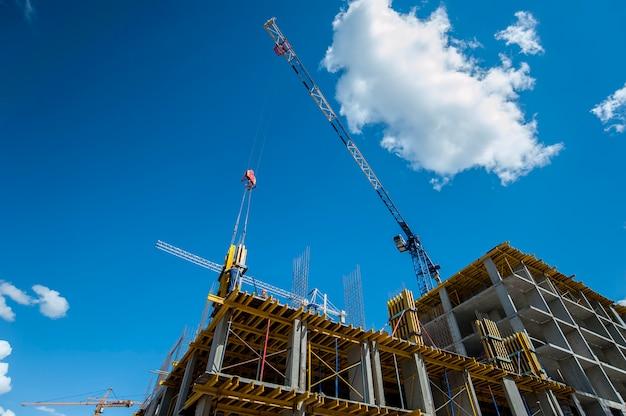 Het monolithische frame van een nieuw huis in aanbouw op de vonn van de kraan en de blauwe lucht
