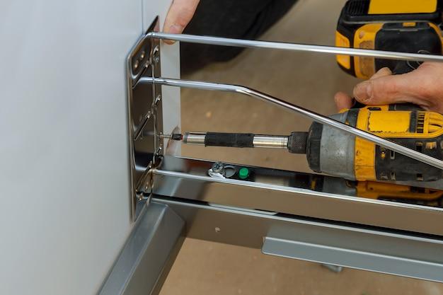 Het monteren van meubels grote grote vuilnisbak schroeven met behulp van een schroevendraaier.