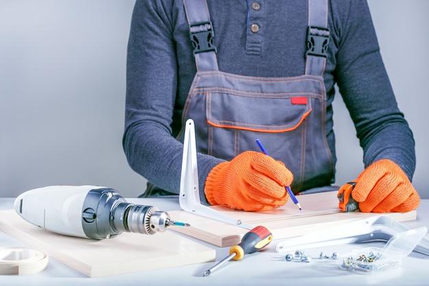 Het monteren van meubels van spaanplaat, met behulp van een schroevendraaier, close-up.