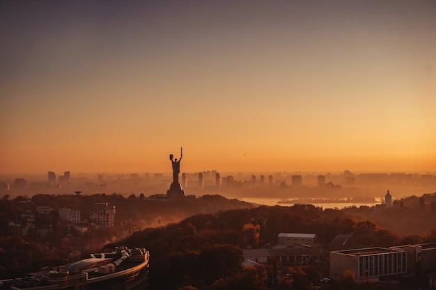 Het monument van het moedervaderland bij zonsondergang. in kiev, oekraïne.