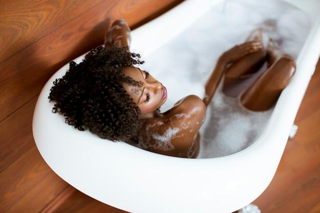 Het mooie afrikaanse amerikaanse vrouw baden in een tonhoogtepunt van schuim
