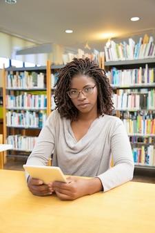 Het mooie afrikaanse amerikaanse vrouw stellen bij bibliotheek