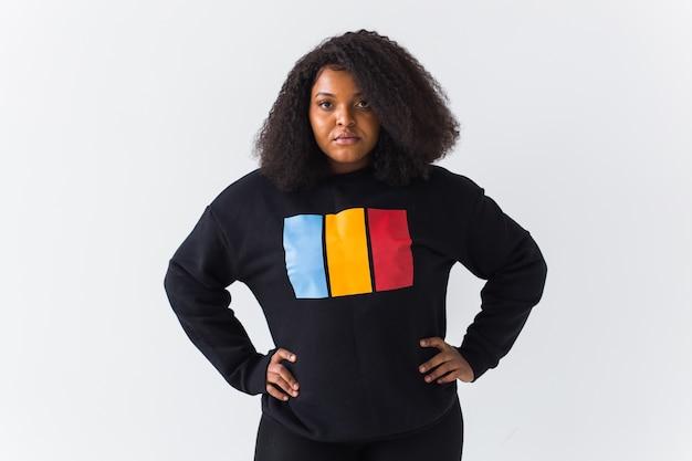 Het mooie afrikaanse amerikaanse vrouw stellen in zwart sweatshirt op een wit