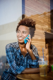 Het mooie afrikaanse meisje glimlachen, die op telefoon spreken, die in koffie zitten. schot van buitenaf.