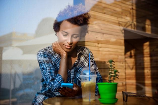 Het mooie afrikaanse meisje glimlachen, die telefoon bekijken, die in koffie zitten. schot van buitenaf.