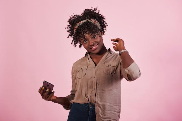 Het mooie afro amerikaanse meisje bevindt zich in de studio met roze achtergrond en houdt telefoon