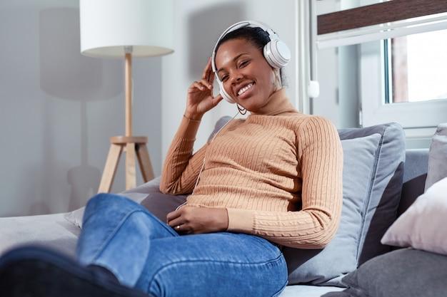 Het mooie afro-amerikaanse meisje met hoofdtelefoons luistert aan muziek