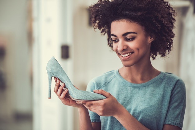 Het mooie amerikaanse meisje kiest schoenen met hoge hakken.