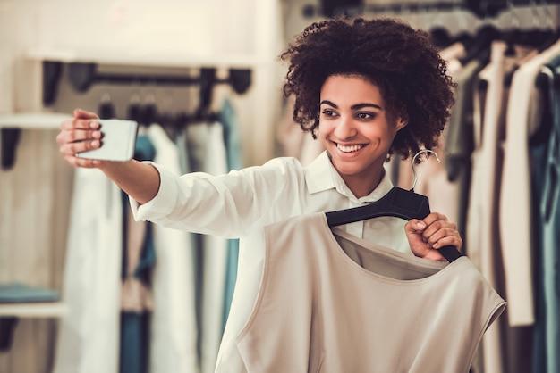 Het mooie amerikaanse meisje van afro kiest kleren.